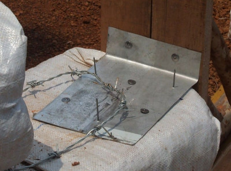 Sheet metal sliders anchor door and window bucks (rough frames) to earthbags.