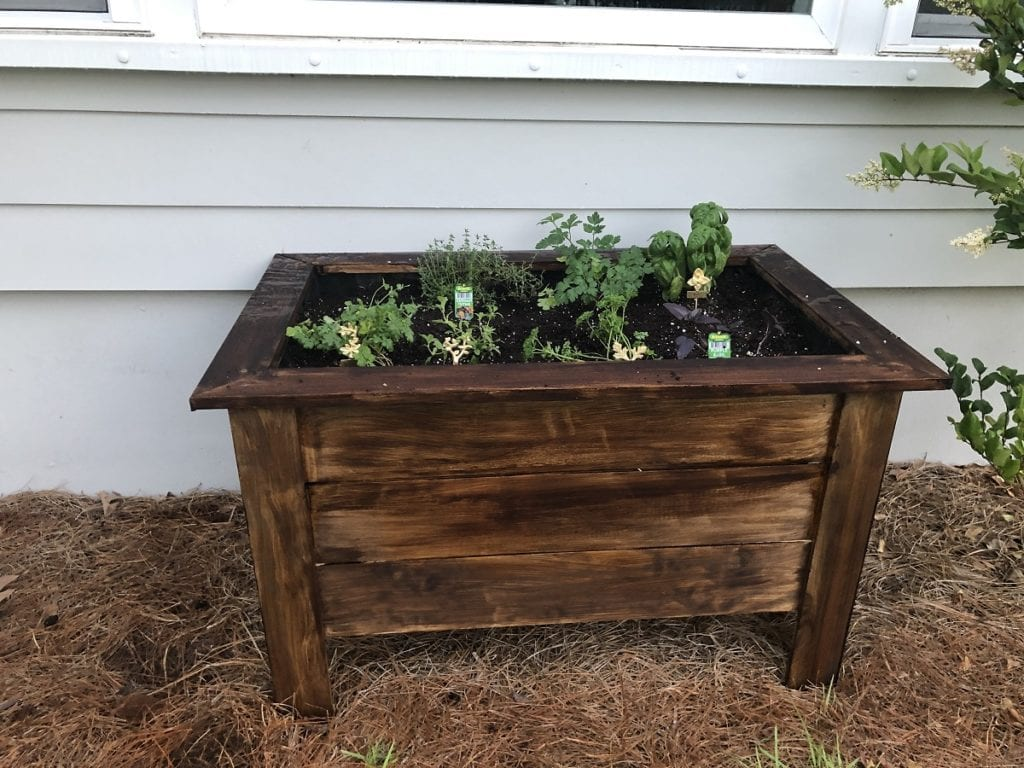 Situate the raised bed in a sunny area, fill with potting soil, and plant your herbs.